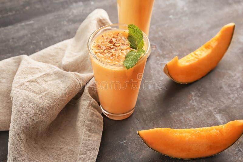 Стекло вкусного smoothie дыни на таблице стоковые фотографии rf
