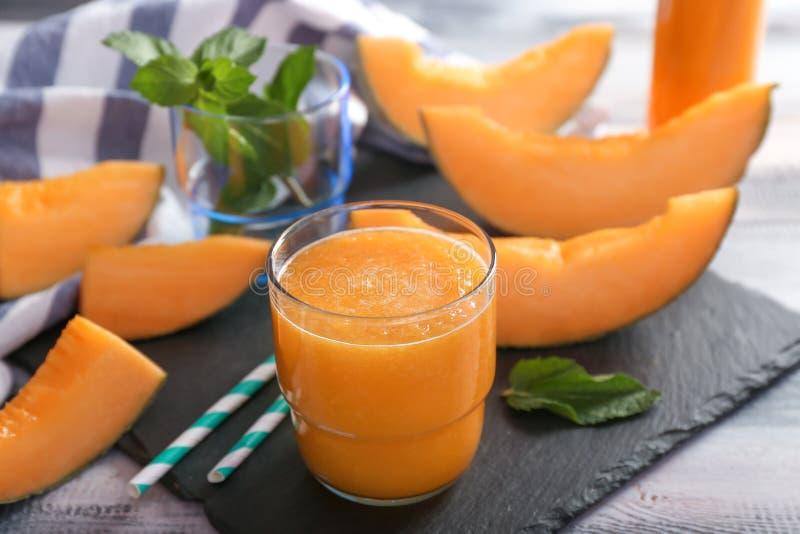 Стекло вкусного smoothie дыни на таблице стоковые изображения rf