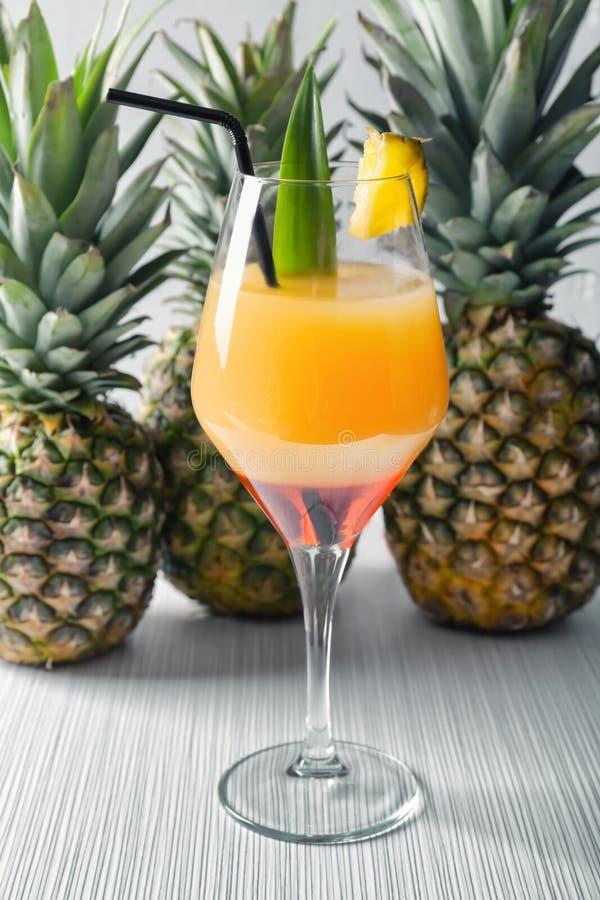 Стекло вкусных коктейля и ананасов ананаса на светлом деревянном столе стоковое изображение rf