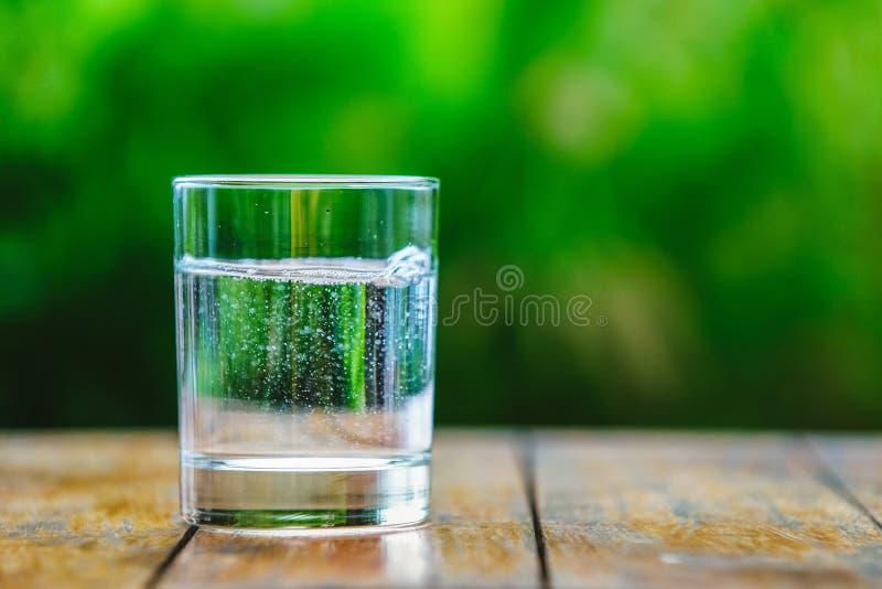 Стекло воды на зеленой предпосылке стоковые изображения