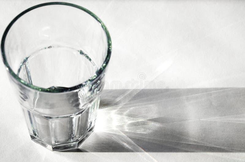 Стекло воды с сильными тенями на белой предпосылке стоковая фотография