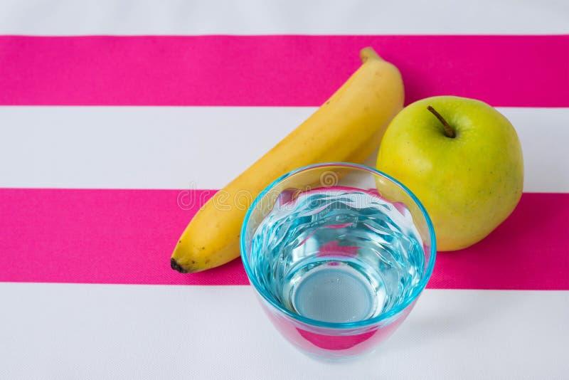Стекло воды, яблока и банана на скатерти стоковые изображения