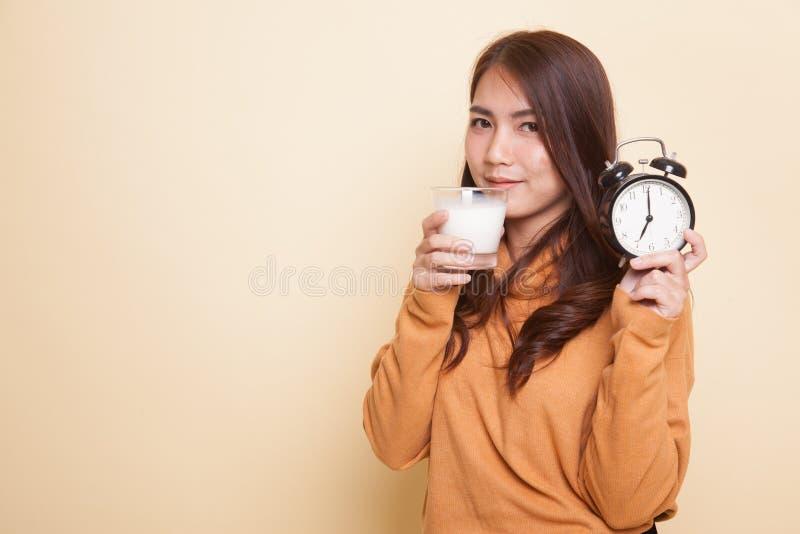 Стекло здоровой азиатской женщины выпивая часов владением молока стоковое фото