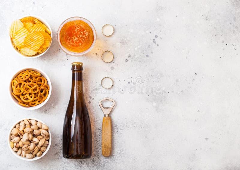 Стекло и бутылка пива лагера ремесла с закуской и консервооткрывателем на каменной предпосылке кухонного стола Крендель и хрустящ стоковое фото