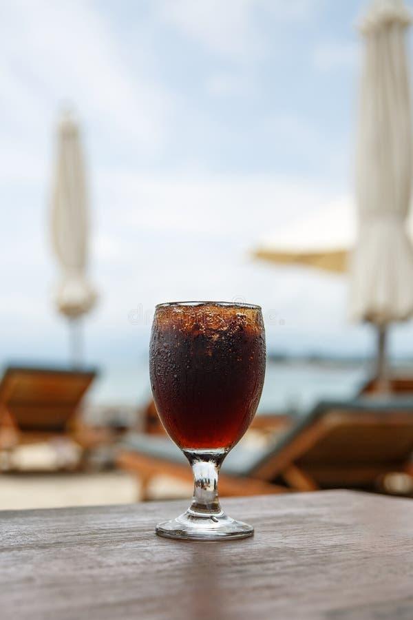 Стекло колы на пляже с зонтиками Охлаждая напиток стоковые изображения rf