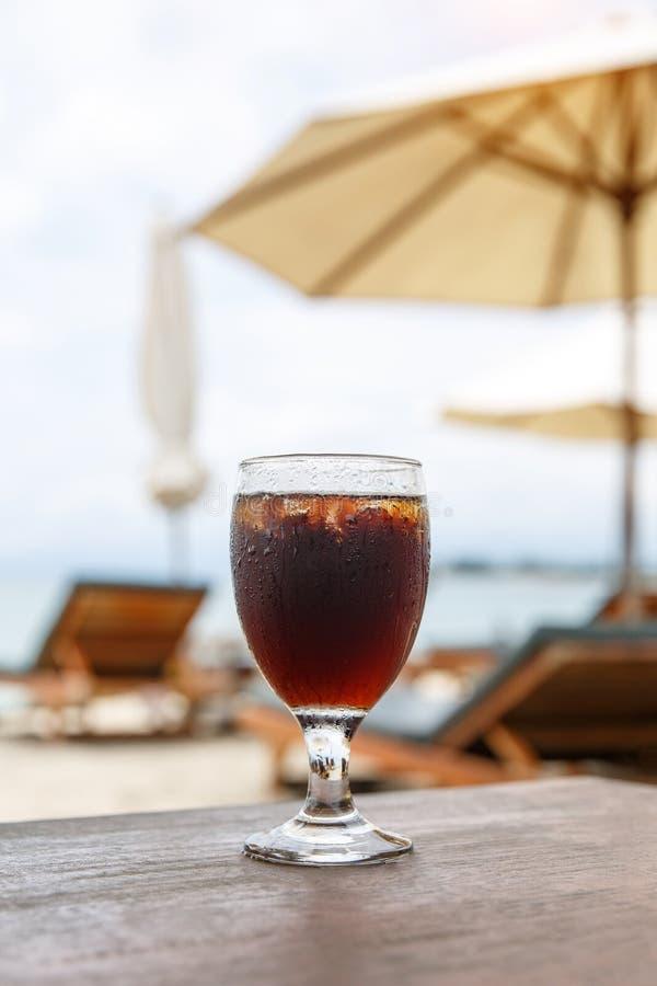 Стекло колы на пляже с зонтиками Охлаждая напиток стоковые изображения