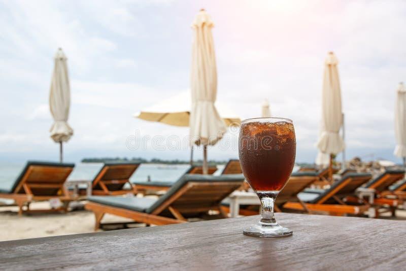 Стекло колы на пляже с зонтиками Охлаждая напиток стоковое фото