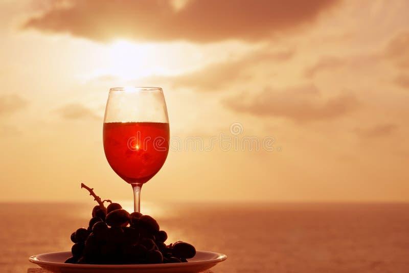 Стекло красного вина на предпосылке моря захода солнца Романтичная концепция даты стоковые изображения