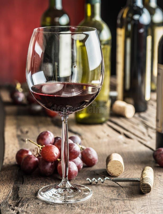 Стекло красного вина на таблице Бутылка и виноградины вина на ба стоковое изображение