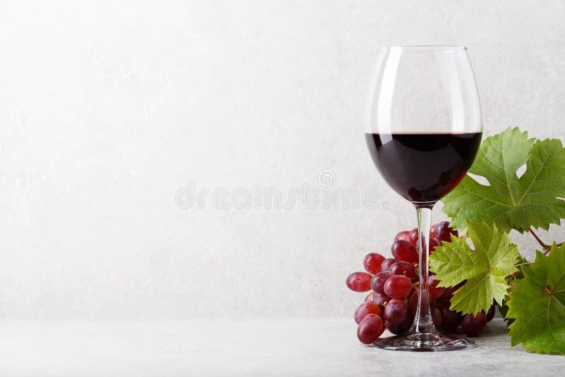 Стекло красного вина на таблице, виноградинах и листьях виноградины : стоковая фотография rf