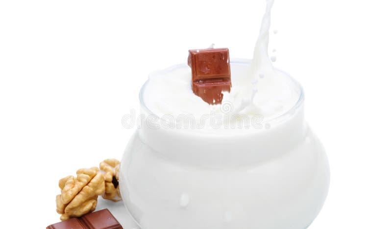 Стекло молока, гаек и части шоколада Шоколад падает в молоко Изолированное фото на белой предпосылке стоковое изображение