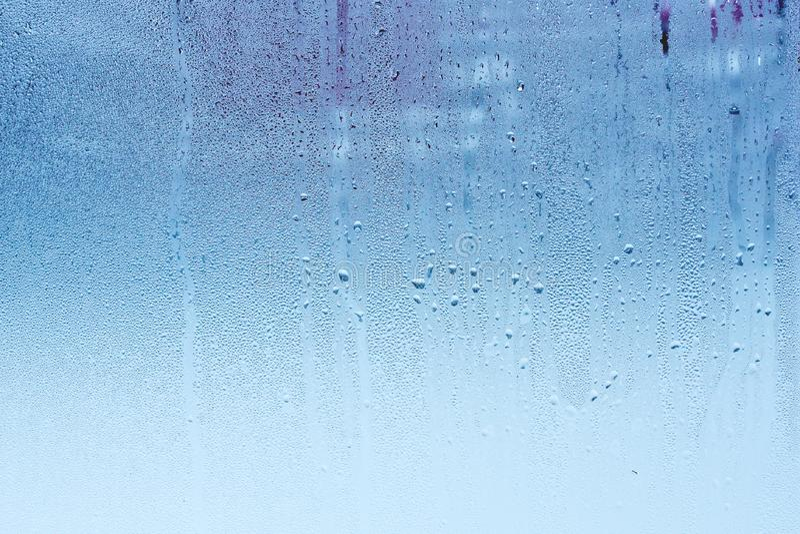 Стекло окна с конденсацией, высокой влажностью в комнате, большими капельками воды, холодным тоном стоковые фото