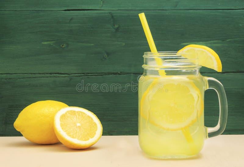 Стекло опарника каменщика лимонада лимона с лимонами и соломой на таблице и деревянной предпосылке стоковая фотография