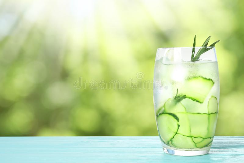 Стекло освежающего напитка с кусками огурца и розмаринового масла на голубом деревянном столе против запачканной предпосылки стоковые фотографии rf