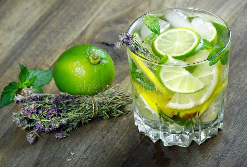 Стекло освежающего напитка стекло холодной воды с льдом, тимианом, мятой и лимоном на деревянном столе r стоковые изображения