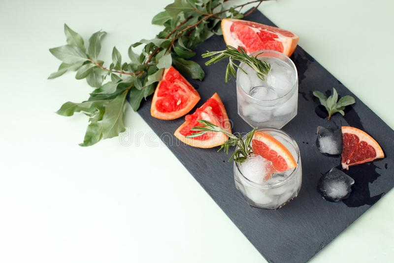 Стекло освежая напитка грейпфрута с розмариновым маслом на таблице, меню курорта лета, концепции тележки бара, космосе экземпляра стоковое фото