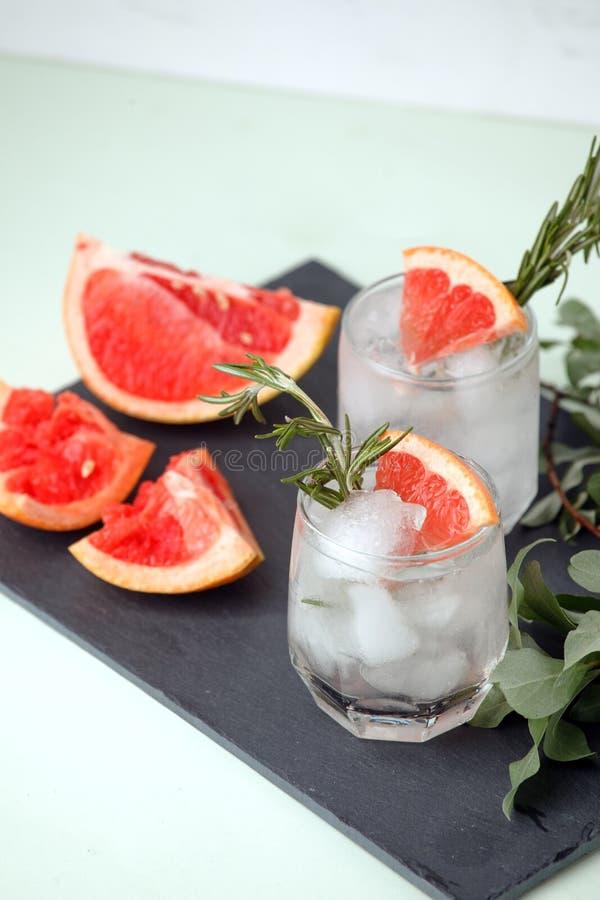 Стекло освежая напитка грейпфрута с розмариновым маслом на таблице, меню курорта лета, концепции тележки бара, космосе экземпляра стоковая фотография