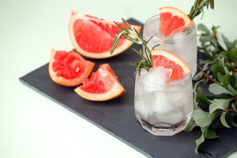 Стекло освежая напитка грейпфрута с розмариновым маслом на таблице, меню курорта лета, концепции тележки бара, космосе экземпляра стоковое изображение rf