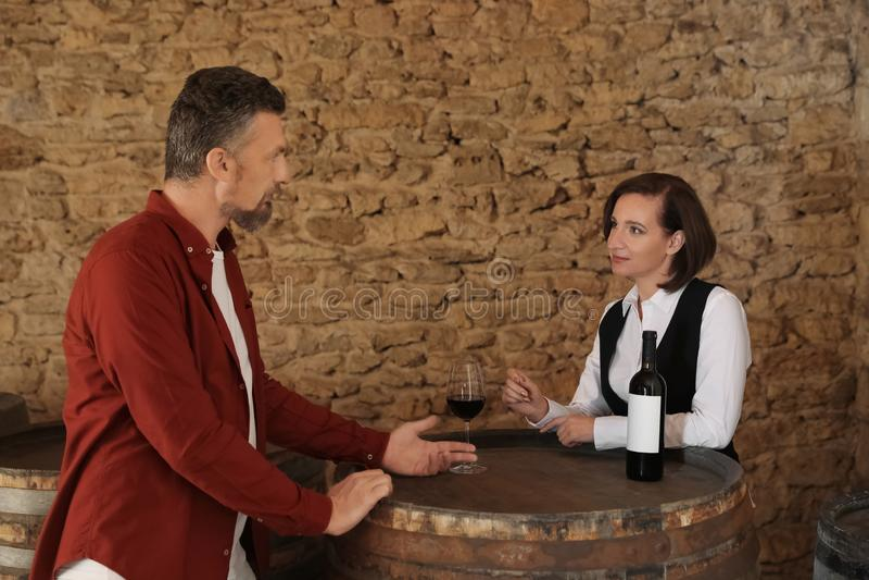 Стекло официантки служа красного вина к клиенту стоковое изображение