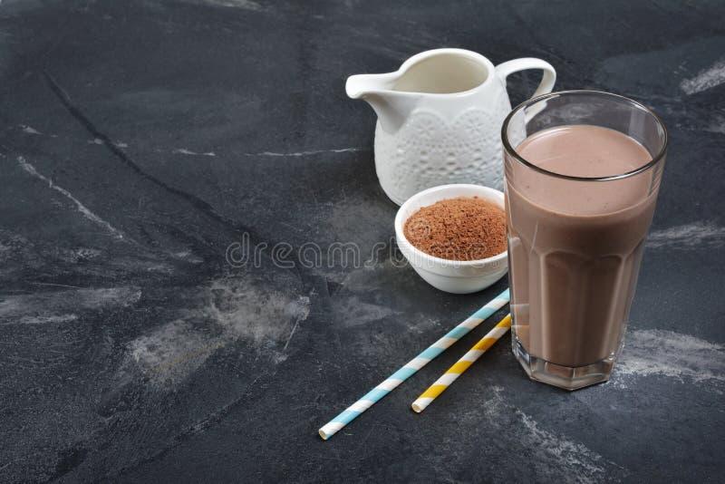 Стекло очень вкусного холодного напитка шоколадного молока с белыми кувшином и бурым порохом стоковые фото