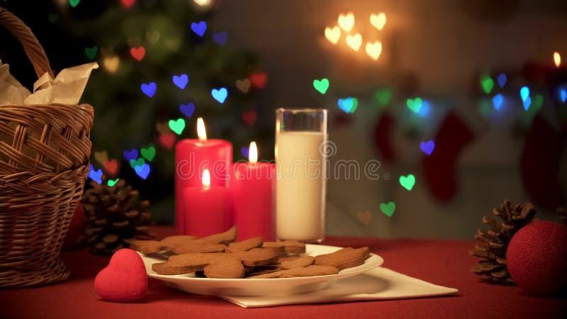 Стекло печениь молока и имбиря на таблице, рождественской елке сверкная со светами стоковые фото