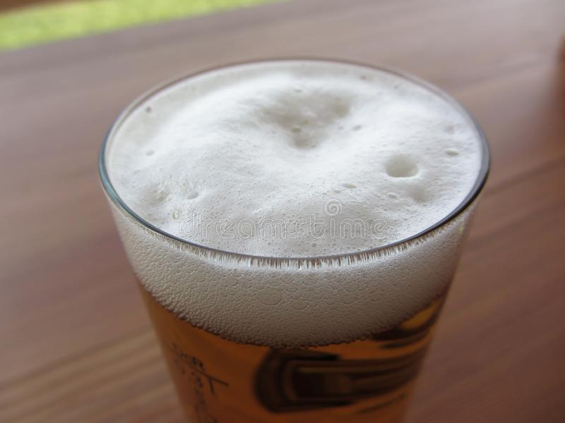 Стекло пива на таблице Крупный план пены пива стоковые фото