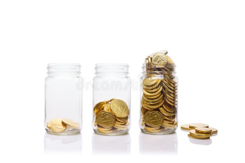 Стекло раздражает с растущим количеством золотых монеток Сбережения и богатство стоковое фото rf
