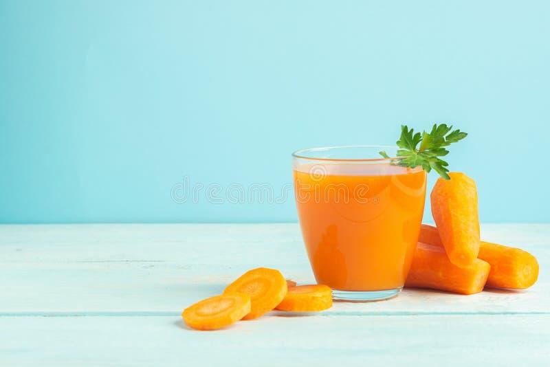 Стекло свежего сока моркови на деревянной голубой предпосылке r r стоковая фотография