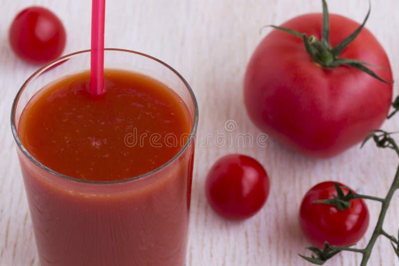 Стекло сока томата и красных томатов на белой предпосылке стоковая фотография rf