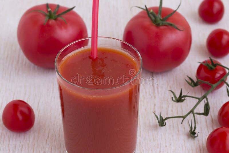 Стекло сока томата и красных томатов на белой предпосылке стоковое фото rf