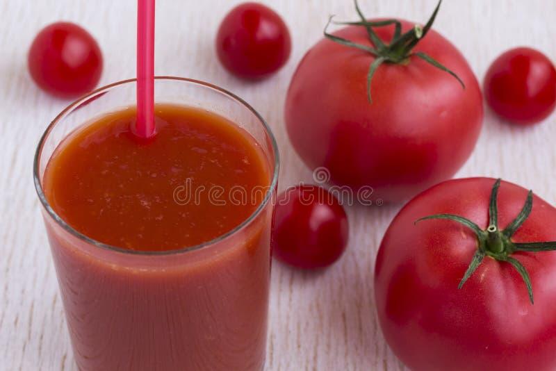 Стекло сока томата и красных томатов на белой предпосылке стоковые фото