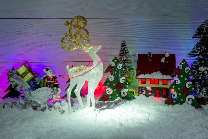 стекло состава рождества bauble голубое Санта Клаус в санях с подарками, олене сказки белом, небольшом доме игрушки стоковое фото