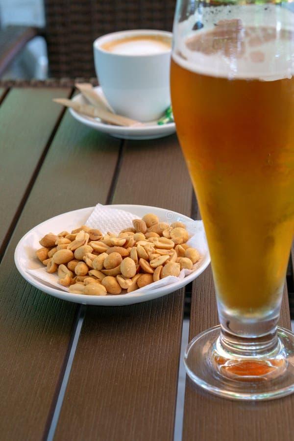 Стекло со светлым пивом, зажаренными в духовке арахисами и чашкой americano на деревянном столе r стоковые изображения