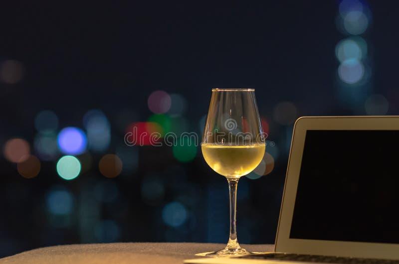 Стекло с белым вином кладет дальше софу с ноутбуком с красочным светом bokeh от города стоковые изображения rf