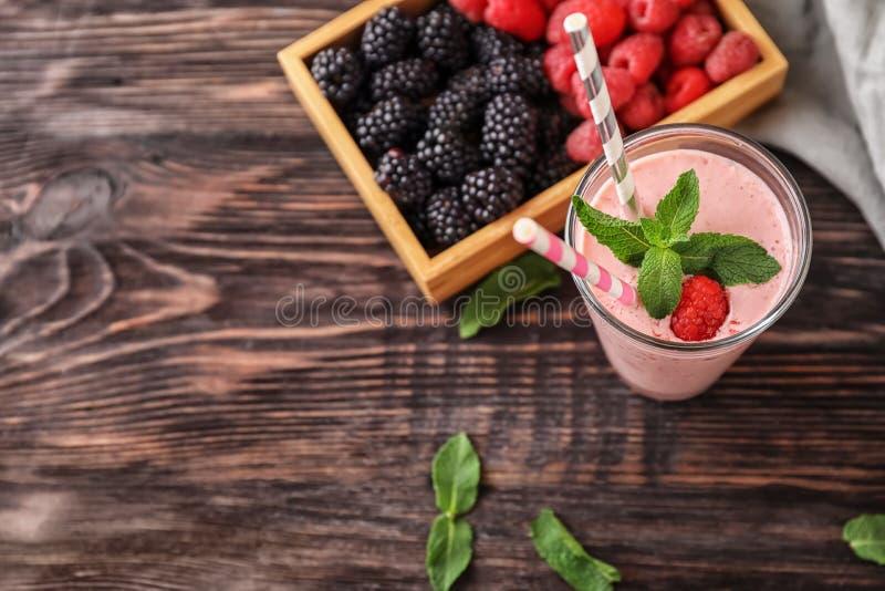 Стекло с вкусными smoothie и ягодами поленики на деревянном столе стоковые изображения