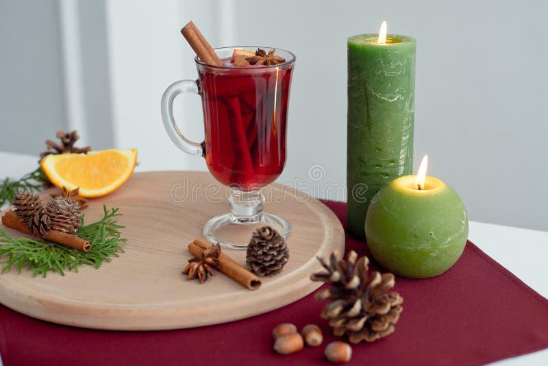 Стекло с горячим красным обдумыванным вином для зимы и рождества с оранжевыми ручками куска, анисовки и циннамона изолированными  стоковое фото rf