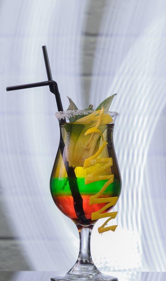 Стекло с коктеилем на стеклянном столе и предпосылке кирпича стоковое изображение