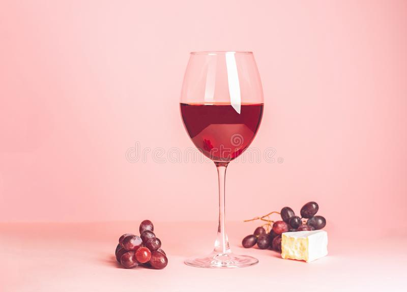 Стекло с красным вином и закуской на чувствительной розовой предпосылке r r minimalism стоковое фото