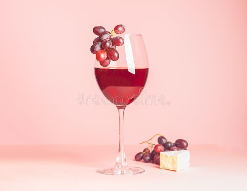 Стекло с красным вином и закуской на чувствительной розовой предпосылке r r minimalism стоковые фото