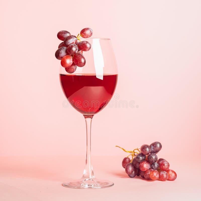 Стекло с красным вином и связка винограда на нежной розовой предпосылке r r minimalism стоковые фото