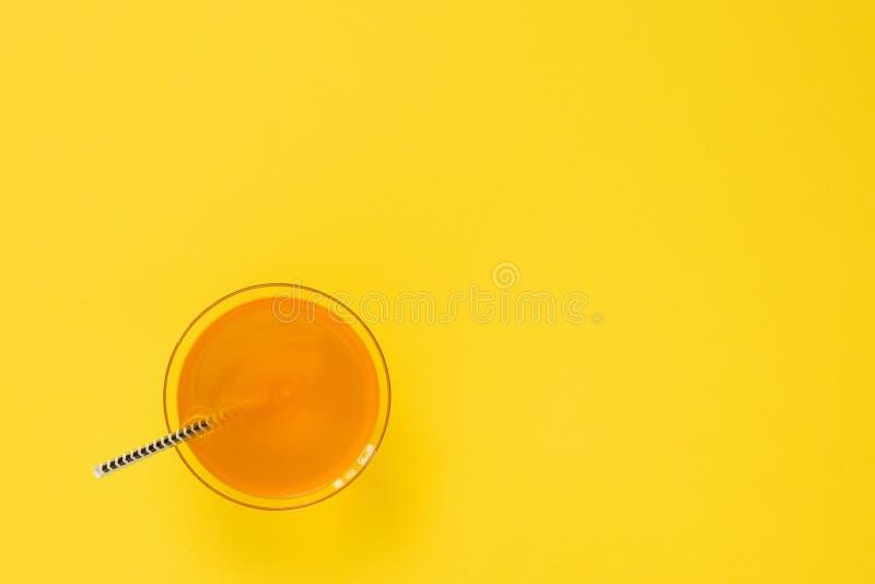 Стекло с соломой оранжевого напитка и коктейля на желтой предпосылке minimalism r стоковое фото rf