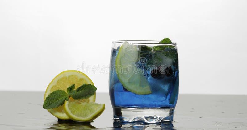 Стекло с холодным голубым напитком с листьями мяты, известки, лимона, черных смородин стоковое изображение