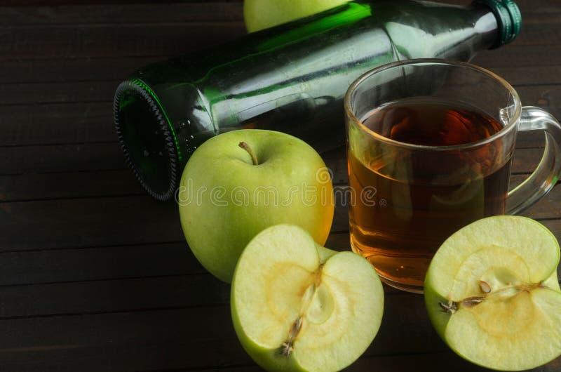 Стекло уксуса яблочного сидра с зелеными яблоками и кладя бутылки сидра на деревянной предпосылке, космосе для текста стоковое фото