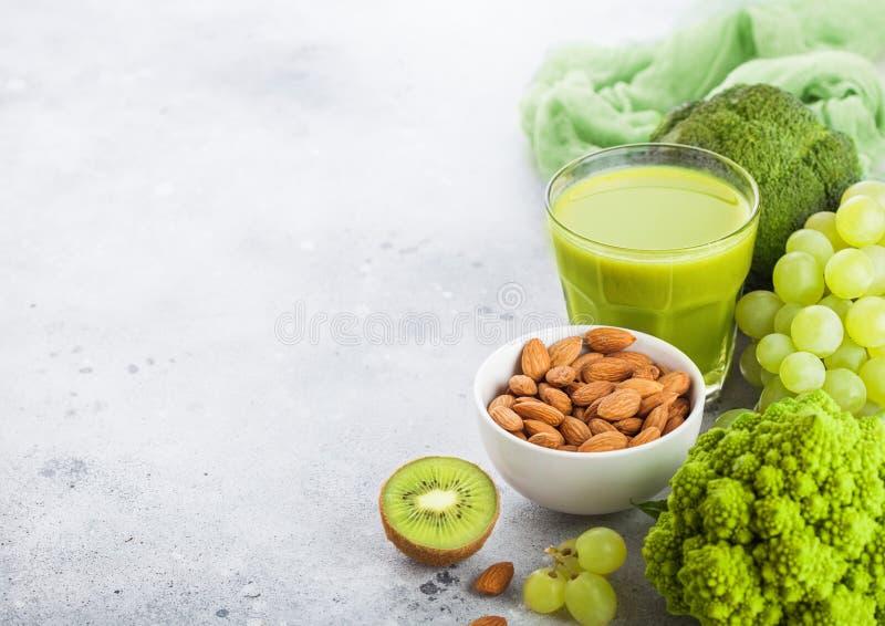 Стекло фрукта и овоща свежего сока smoothie органического зеленого тонизированного на каменной предпосылке кухни С гайками миндал стоковые фото