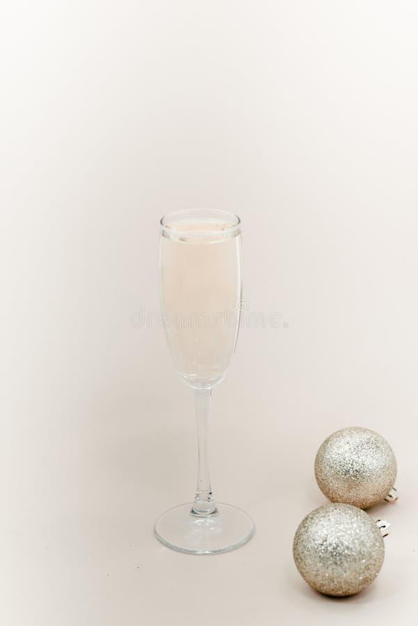 Стекло шампанского с пузырями Белые шарики предпосылки и рождества стоковые фотографии rf