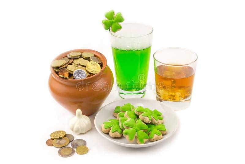 Стекло яркого зеленого цвета пива с стеклом клевера питья вискиа золотого с льдом и глиняным горшком с торжеством сокровища везен стоковые изображения