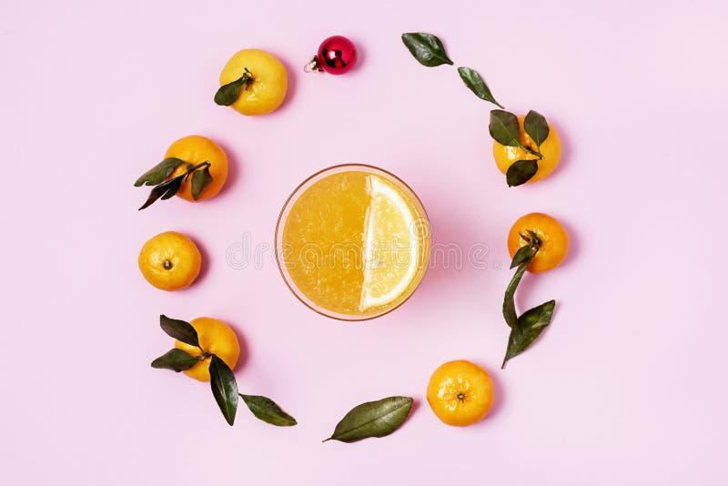 Стекло Citrus Juices Detox Diet Healthy Drink Mandarine и Lemon и Juices Raw Mandarines и Christmas Balls Pink Фон стоковая фотография rf