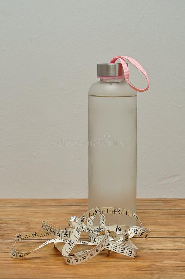 Стеклянная бутылка заполнила с льдом - холодной водой и измеряя лентой стоковые фотографии rf