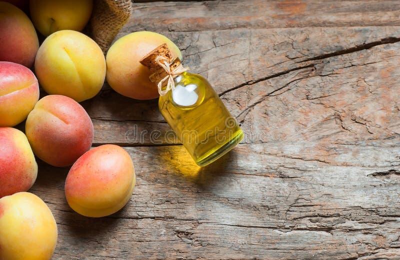 Стеклянная бутылка олеума armeniaca сливы масла стерженя семени абрикоса со свежими зрелыми плодами абрикоса стоковые изображения rf