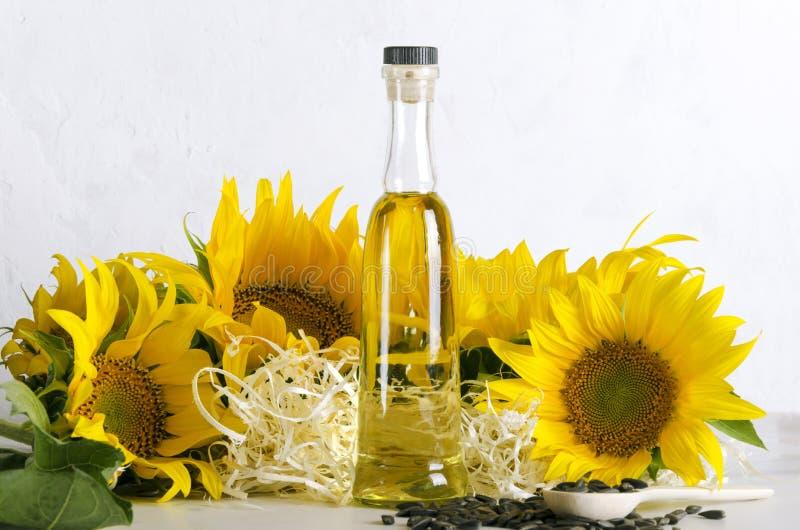 Стеклянная бутылка подсолнечного масла, семян, деревянных щепок и шикарных солнцецветов на белой таблице против белой стены стоковое изображение